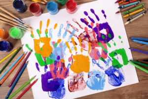Painted handprints with art and craft equipment on a school table.